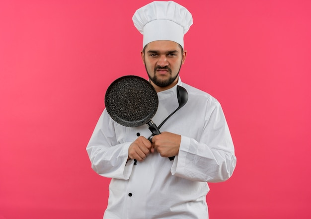 ピンクの空間で孤立して見えるフライパンとおたまを保持しているシェフの制服を着た不機嫌な若い男性料理人