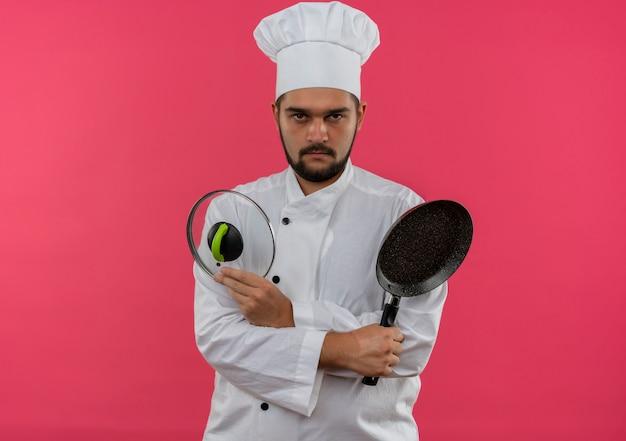 ピンクのスペースで孤立して見えるフライパンと鍋の蓋を保持しているシェフの制服を着た不機嫌な若い男性料理人