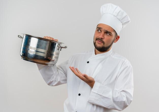 不機嫌そうな若い男性料理人が白いスペースで隔離された側を見て空の手を示す鍋を保持しているシェフの制服を着て