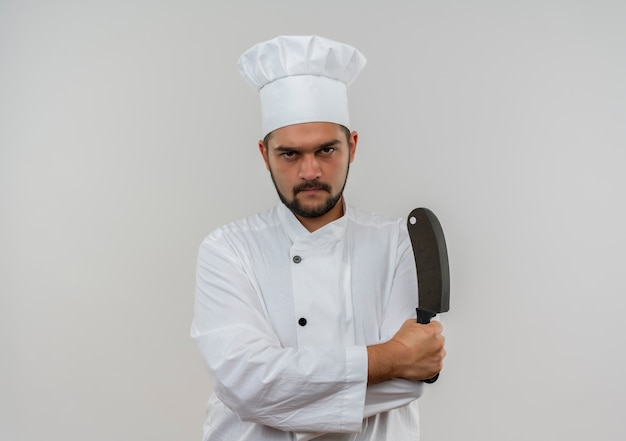閉じた姿勢で立って、白いスペースで隔離の包丁を保持しているシェフの制服を着た不機嫌な若い男性料理人