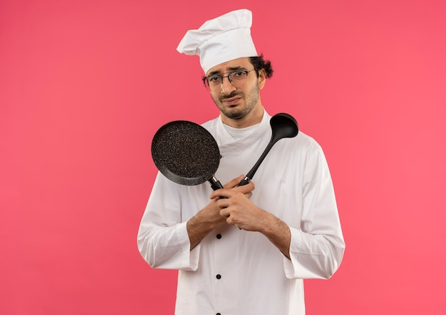 ピンクのフライパンとヘラを持って交差するシェフの制服とメガネを身に着けている不機嫌な若い男性料理人