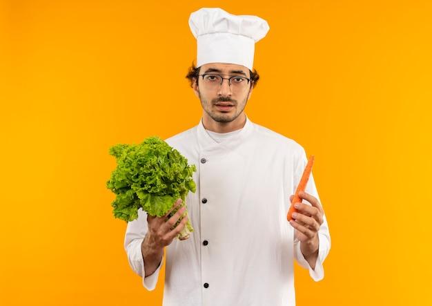 노란색 벽에 고립 된 샐러드와 당근을 들고 요리사 유니폼과 안경을 쓰고 불쾌한 젊은 남성 요리사