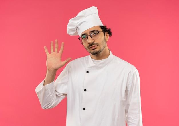 ピンクの壁に隔離された停止ジェスチャーを示すシェフの制服と眼鏡を身に着けている不機嫌な若い男性料理人