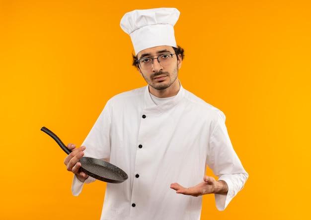 Giovane cuoco maschio dispiaciuto che indossa l'uniforme del cuoco unico e vetri che tengono la padella e spalmano la mano isolata sulla parete gialla