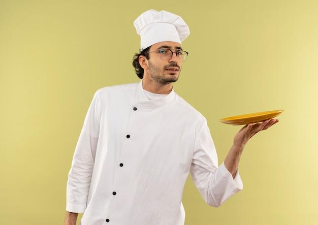 Giovane cuoco maschio dispiaciuto che indossa l'uniforme dello chef e bicchieri tenendo il piatto