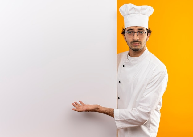 Unpleased young male cook wearing chef uniform and glasses holding and showing with hand to white wall isolated on yellow wall with copy space