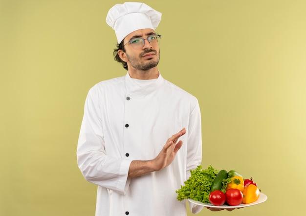 Giovane cuoco maschio dispiaciuto che indossa l'uniforme dello chef e bicchieri tenendo le verdure sul piatto e mostrando il gesto di arresto