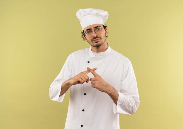 Giovane cuoco maschio dispiaciuto che indossa l'uniforme dello chef e gli occhiali che mostrano il gesto di no