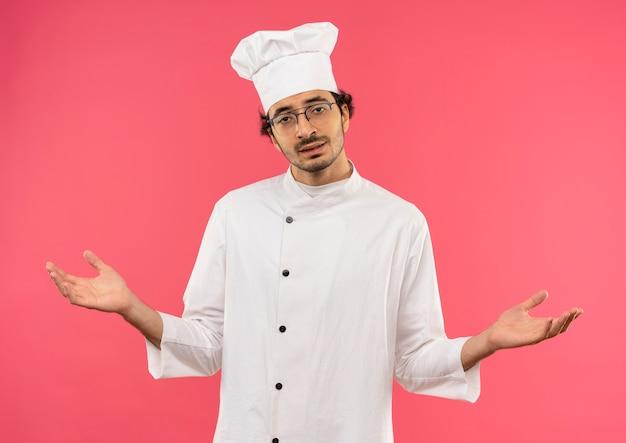 Il giovane cuoco maschio dispiaciuto che indossa l'uniforme e gli occhiali del cuoco unico si diffonde le mani isolate sulla parete rosa
