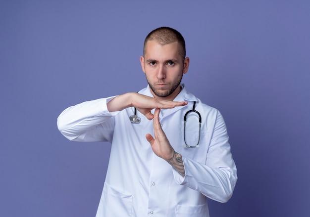 コピースペースで紫色の背景に分離されたタイムアウトジェスチャーを行う彼の首に医療ローブと聴診器を身に着けている不機嫌な若い男性医師