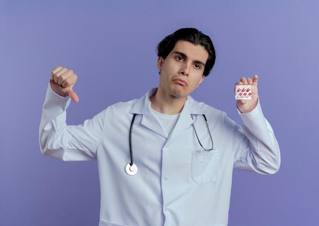 医療用ローブと聴診器を身に着けている不機嫌な若い男性医師は、紫色の壁に隔離された医療カプセルと親指を下に表示している側を見て