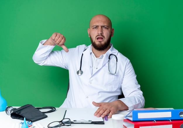 의료 가운과 청진기를 착용하고 의료 도구를 사용하여 책상에 앉아 불쾌한 젊은 남성 의사가 녹색 벽에 고립 된 자신의 엄지 손가락