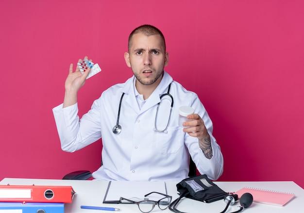 의료 비커와 분홍색 배경에 고립 된 정제 및 캡슐의 팩을 들고 작업 도구로 책상에 앉아 의료 가운과 청진기를 입고 불쾌한 젊은 남성 의사