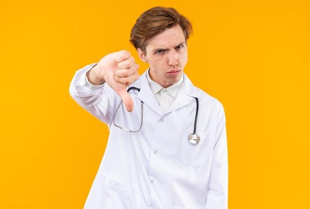 オレンジ色の壁に隔離された親指を示す聴診器と医療ローブを身に着けている不機嫌な若い男性医師