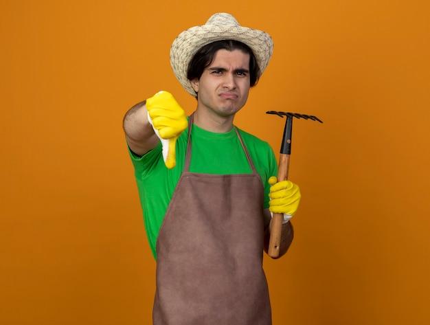 オレンジ色に分離された親指を下に示しているくわ熊手を保持している手袋と園芸帽子を身に着けている制服を着た不機嫌な若い男性の庭師