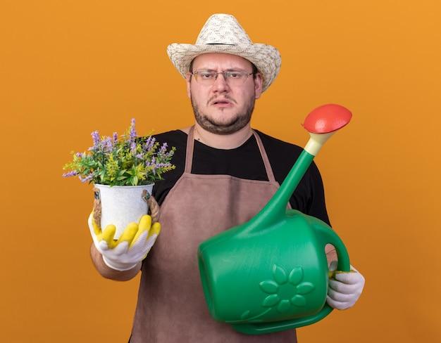 じょうろを保持している園芸帽子と手袋を身に着けている不機嫌な若い男性の庭師は、オレンジ色の壁に隔離された植木鉢で花を差し出すことができます