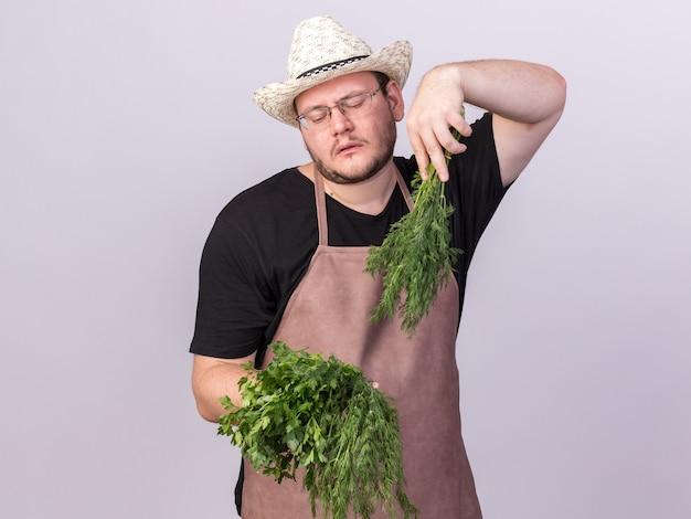 Giovane giardiniere maschio dispiaciuto che porta il cappello di giardinaggio che tiene e che esamina aneto con coriandolo isolato sulla parete bianca