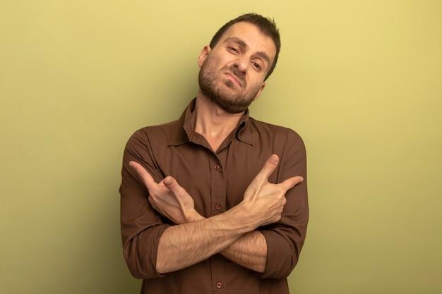 オリーブグリーンの壁に隔離された側面を指して手を交差させている不機嫌な若い男