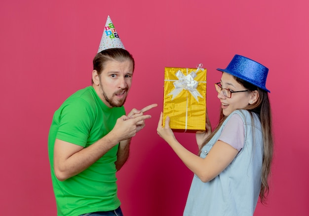 Unpleased young man wearing party hat looks pointing at gift box holding by young girl wearing blue party hat isolated on pink wall