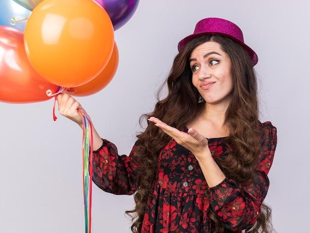 白い壁に隔離された風船を見て、手で指しているパーティーハットを身に着けている不機嫌な若いパーティーの女の子