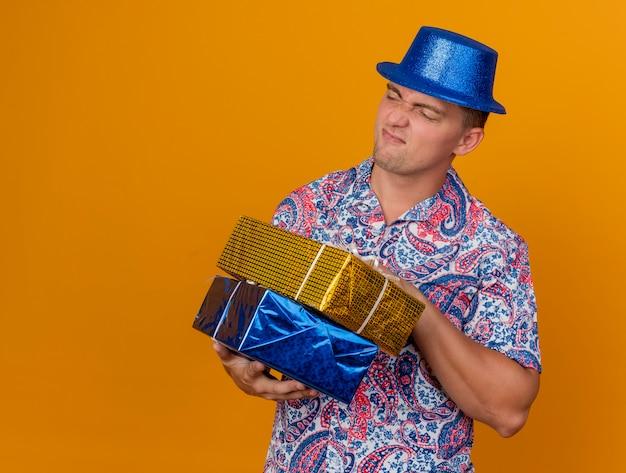 コピースペースでオレンジ色の背景に分離されたギフトボックスを保持している青い帽子をかぶって側を見て不機嫌な若いパーティー男
