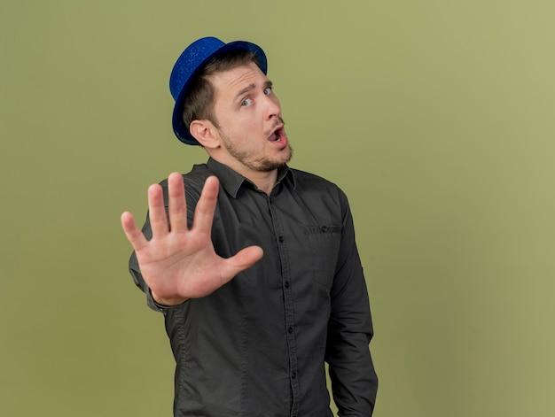 검은 셔츠와 올리브 그린에 고립 된 중지 제스처를 보여주는 파란색 모자를 쓰고 불쾌한 젊은 파티 남자