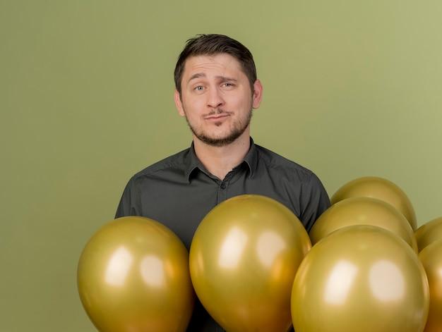 Ragazzo di partito giovane insoddisfatto che indossa la camicia nera in piedi tra palloncini isolati su verde oliva