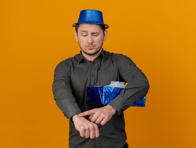 Ragazzo di partito giovane insoddisfatto che indossa il cappello blu che tiene il contenitore di regalo e che mostra il gesto dell'orologio da polso isolato sull'arancio