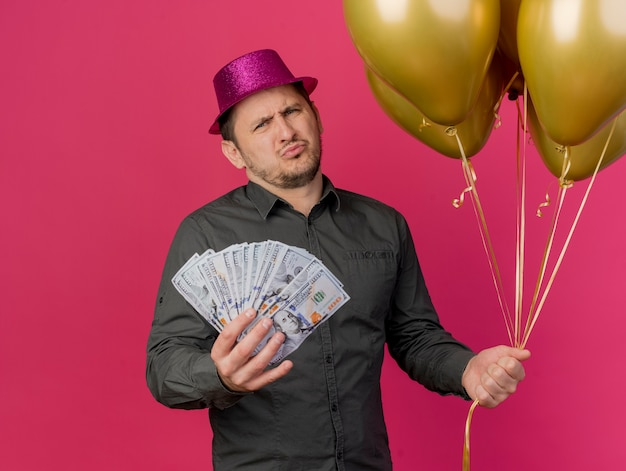 Unpleased young party guy wearing pink hat holding balloons with cash isolated on pink