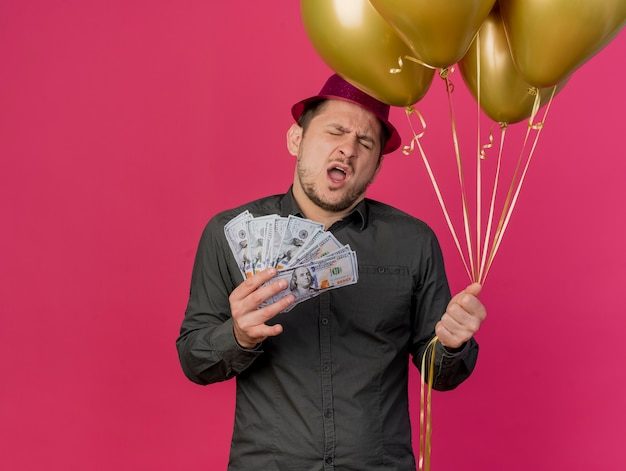 Unpleased young party guy with closed eyes wearing pink hat holding balloons and cash isolated on pink