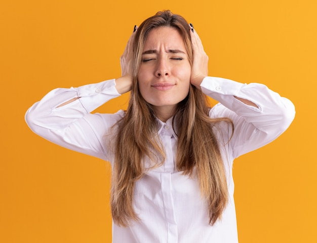 Unpleased young pretty caucasian girl closes ears with hands isolated on orange wall with copy space