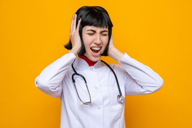 Una giovane ragazza piuttosto caucasica scontenta in uniforme da medico con uno stetoscopio che si copre le orecchie con le mani