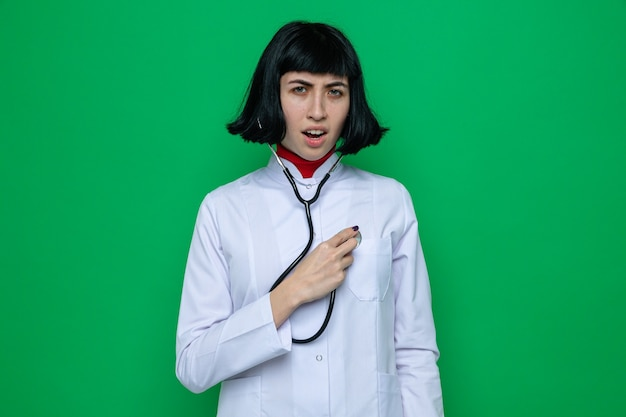 Unpleased young pretty caucasian girl in doctor uniform with stethoscope listening her heartbeat with stethoscope