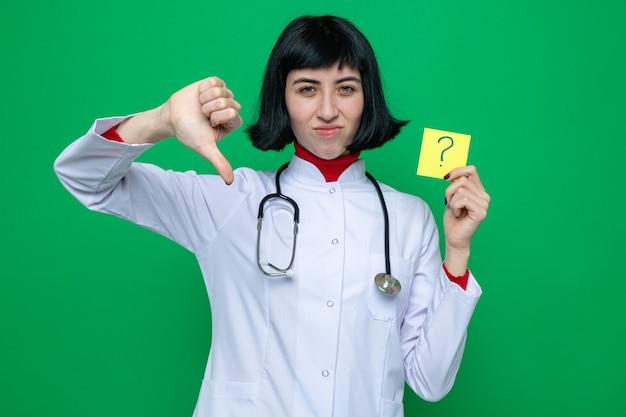 Una giovane ragazza piuttosto caucasica scontenta in uniforme da medico con lo stetoscopio che abbassa il pollice e tiene in mano una nota di domanda