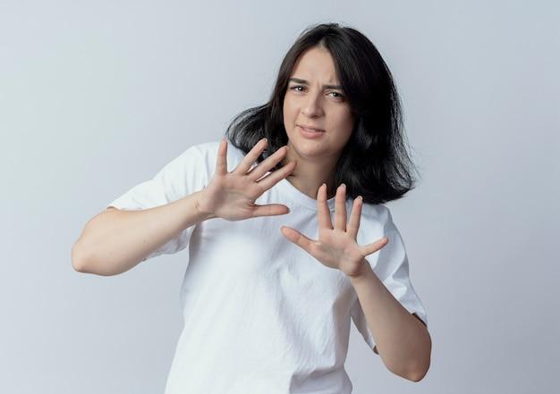 Недовольная молодая симпатичная кавказская девушка, показывающая нет на камеру, изолированную на белом фоне