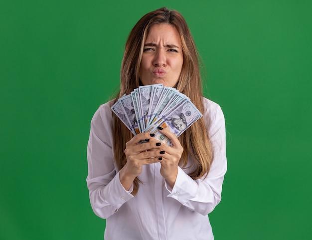 La giovane ragazza abbastanza caucasica scontenta tiene i soldi isolati sulla parete verde con lo spazio della copia