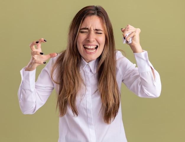불쾌한 젊은 백인 소녀는 손을 들고 서 있고 복사 공간이 있는 올리브 녹색 벽에 격리된 손에 종이를 누릅니다.