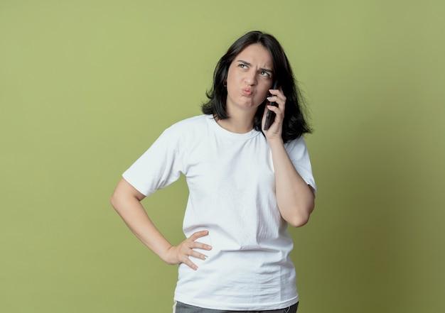 コピースペースとオリーブグリーンの背景で隔離の腰に手を置く側を見て電話で話している不機嫌な若いかなり白人の女の子
