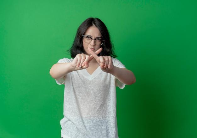 Недовольная молодая симпатичная кавказская девушка в очках, не делающая жестов в камеру, изолирована на зеленом фоне с копией пространства
