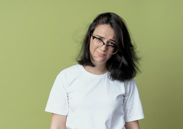 Недовольная молодая симпатичная кавказская девушка в очках смотрит в камеру, изолированную на оливково-зеленом фоне с копией пространства