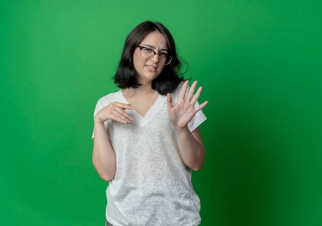 手で5つを示し、コピースペースで緑の背景に隔離された別の1つを空中に保つ眼鏡をかけている不機嫌な若いかなり白人の女の子