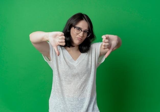 コピースペースで緑の背景に分離された親指を下に示す眼鏡をかけている不機嫌そうな若いかなり白人の女の子