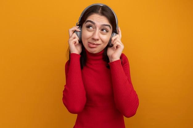 Una giovane ragazza piuttosto caucasica scontenta che indossa e afferra le cuffie guardando il lato che mostra la lingua