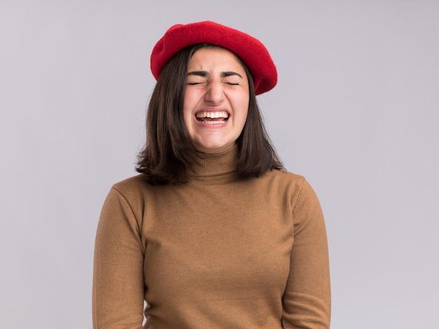 コピースペースで白い壁に隔離された目を閉じて立っているベレー帽の帽子を持つ不機嫌な若いかなり白人の女の子