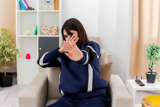 Giovane donna abbastanza caucasica dispiaciuta che si siede sulla poltrona nel soggiorno progettato nascondendo il viso dietro la mano facendo il gesto di arresto