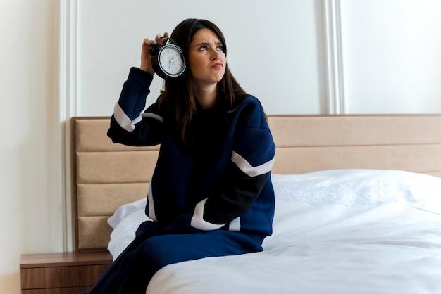 横を見て頭の近くに目覚まし時計を保持している寝室のベッドに座っている不機嫌な若いかなり白人女性