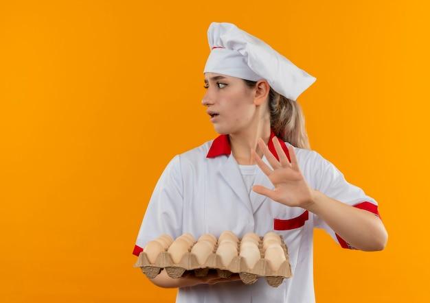 Soddisfatto giovane cuoco grazioso in cartone uniforme della holding del cuoco unico delle uova che esaminano il lato e che gesticolano nessun isolato sullo spazio arancione