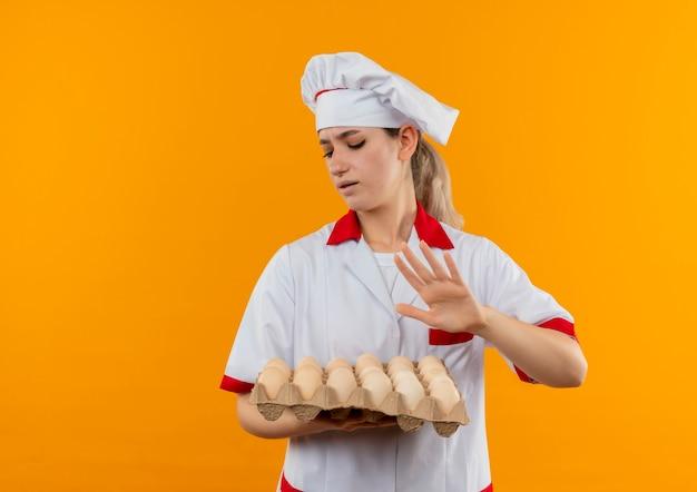 Soddisfatto giovane cuoco grazioso in uniforme del cuoco unico che tiene e che esamina il cartone delle uova e che gesticola non isolato sullo spazio arancione