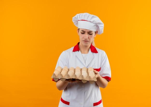 Giovane cuoco poco soddisfatto in uniforme del cuoco unico che tiene e che esamina il cartone delle uova isolato sullo spazio arancione