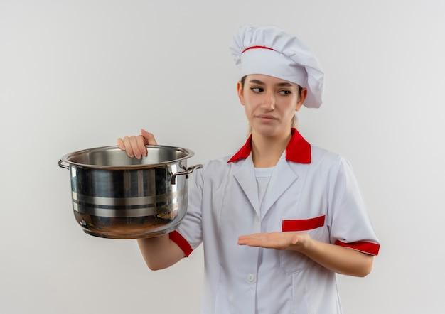 鍋を持って、それを手で指して、白いスペースで隔離された側を見て、シェフの制服を着た不機嫌な若いかわいい料理人